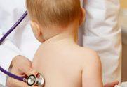 Na foto um médico examina os pulmões de um bebe